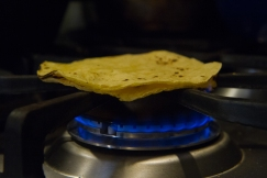 Toasting tortillas on a gas burner.