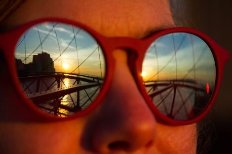 Sunset on the Brooklyn Bridge reflecting in Jamie's glasses.