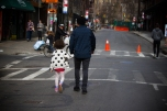 A father and daughter strolling through the Lower East Side on a sunny Sunday.
